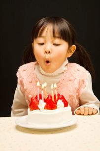 ケーキにのったローソクの火を消す女の子の写真素材 [FYI01537023]