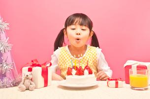 ケーキにのったローソクの火を消す女の子の写真素材 [FYI01537220]