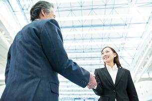 笑顔で握手をするビジネスマンとビジネスウーマンの写真素材 [FYI01537298]