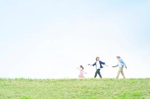 丘の上を歩く日本人家族の写真素材 [FYI01537346]