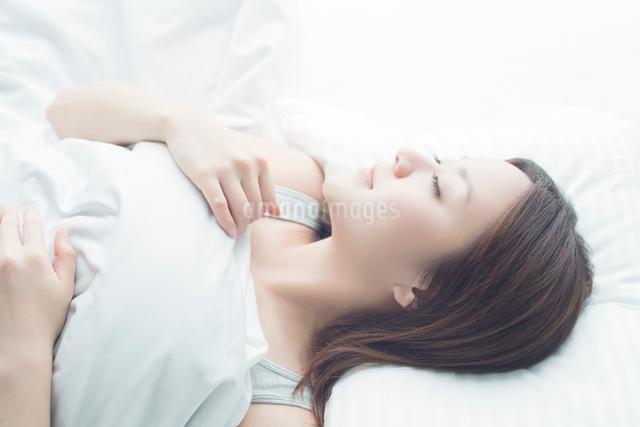 ベッドで眠る日本人女性の写真素材 [FYI01537424]