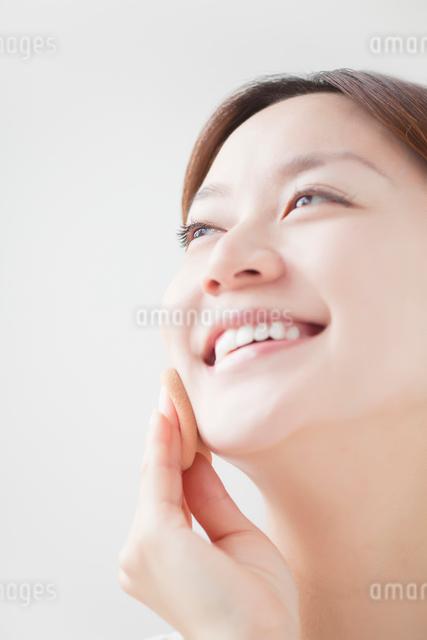 ファンデーションを塗る笑顔の女性の写真素材 [FYI01537487]