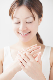 ハンドケアしながら微笑む日本人女性の写真素材 [FYI01537513]