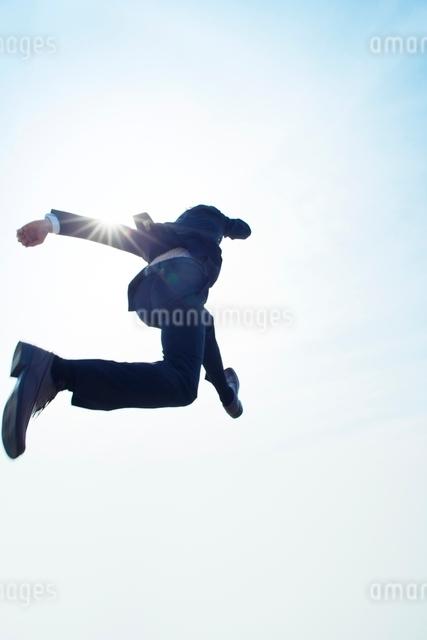 ジャンプするビジネスマンの後ろ姿の写真素材 [FYI01537523]