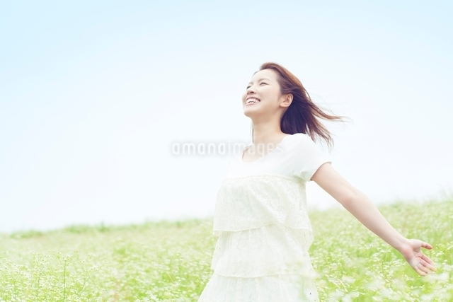 草原に立つ笑顔の女性の写真素材 [FYI01537566]