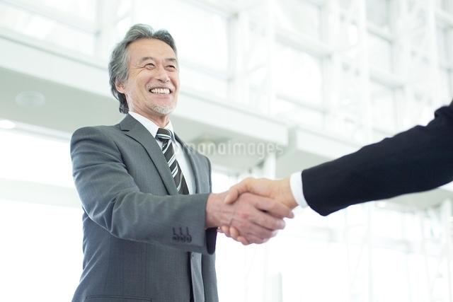 笑顔で握手をする日本人シニアビジネスマンの写真素材 [FYI01537571]