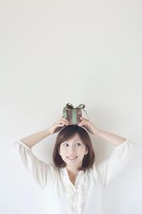 プレゼントボックスを頭にのせる女性の写真素材 [FYI01537603]