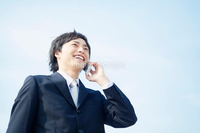 携帯電話を持つ笑顔のビジネスマンの写真素材 [FYI01537636]