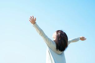 空を見上げて手を伸ばす女性の写真素材 [FYI01537686]
