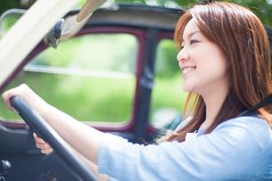 運転席に座りハンドルを握る笑顔の女性の写真素材 [FYI01537790]
