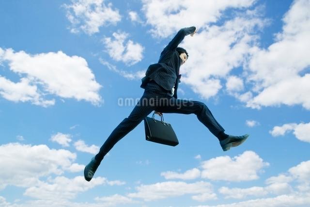 ジャンプするビジネスマンと青空の写真素材 [FYI01537813]