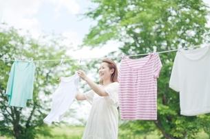笑顔で洗濯物を干す若い女性の写真素材 [FYI01537946]