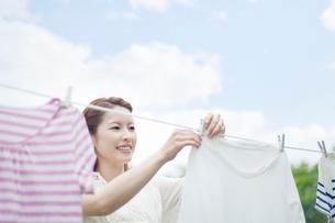笑顔で洗濯物を干す若い女性の写真素材 [FYI01537972]