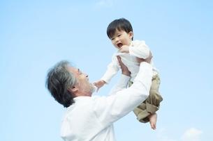 孫を抱き上げる笑顔の祖父の写真素材 [FYI01538020]