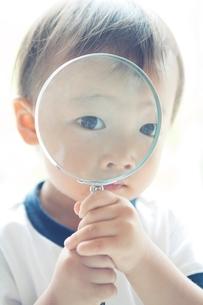 虫メガネを持つ男の子の写真素材 [FYI01538041]