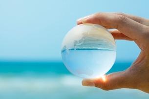 水平線とガラスの地球を持つ手の写真素材 [FYI01538174]