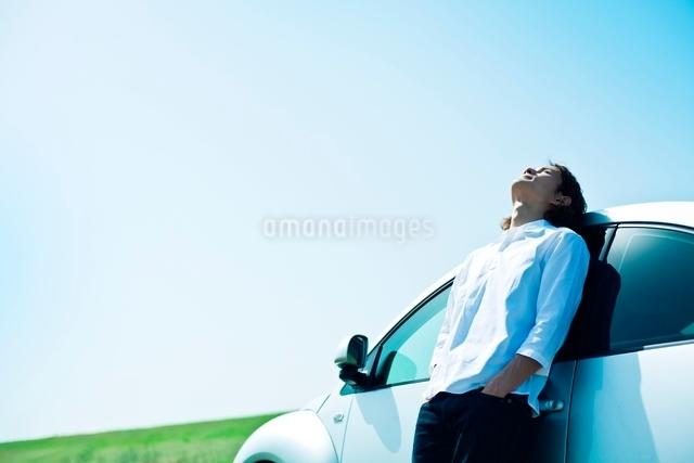 自動車にもたれて空を見上げる男性の写真素材 [FYI01538185]