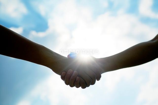 握手する2人の手と太陽の写真素材 [FYI01538192]