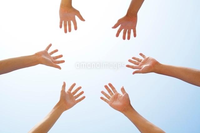 青空に伸ばした3人の手の写真素材 [FYI01538193]