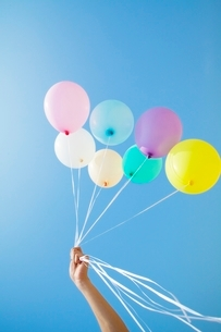 青空と風船を持つ手の写真素材 [FYI01538211]