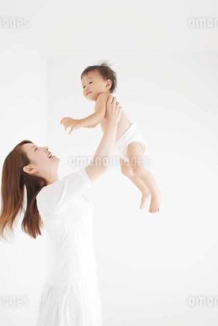 赤ちゃんを抱き上げる笑顔の母親の写真素材 [FYI01538276]