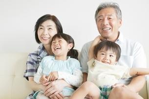 ソファに座る笑顔の孫と祖父母の写真素材 [FYI01538374]
