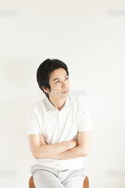 イスに座り腕組みをして見上げる日本人男性の写真素材 [FYI01538437]