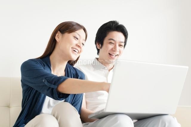ソファに座りパソコンをのぞきこむ笑顔のカップルの写真素材 [FYI01538439]