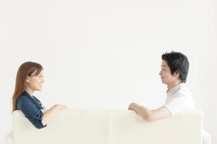 ソファに座り見つめ合う男女の写真素材 [FYI01538449]
