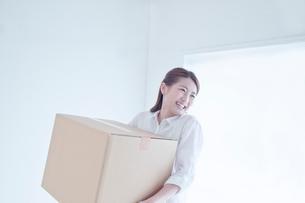 段ボール箱を持つ笑顔の女性の写真素材 [FYI01538482]
