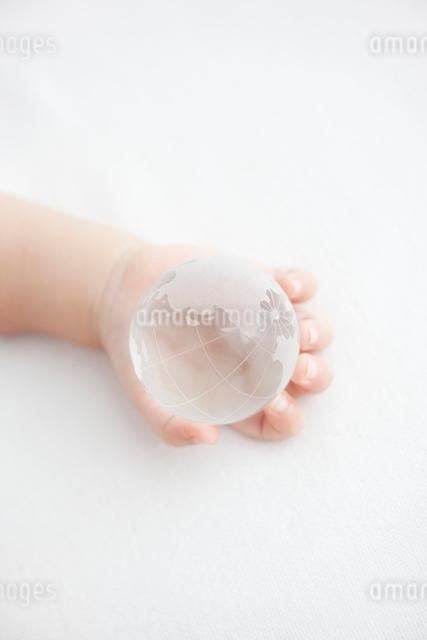 ガラスの地球を持つ赤ちゃんの手元の写真素材 [FYI01538822]
