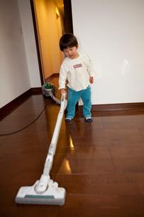 掃除機をかける二歳の男の子の写真素材 [FYI01556679]