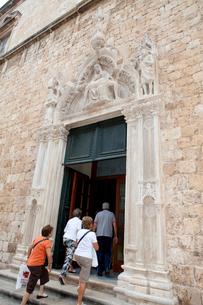 フランシスコ会修道院入口の死のキリストと観光客の写真素材 [FYI01557347]