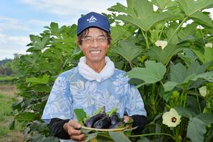 収穫したナスとオクラを持つ農夫の写真素材 [FYI01560126]