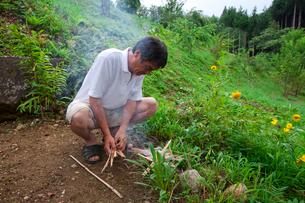 お盆の迎え火を起こす男性の写真素材 [FYI01560484]