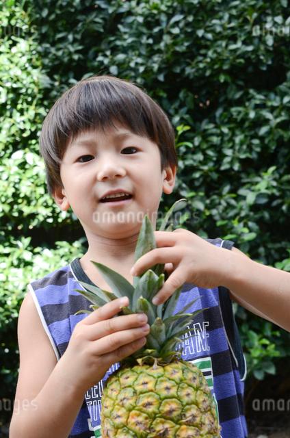 パインナップルを持つ男児の写真素材 [FYI01560831]