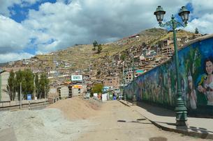 先住民の絵が描かれた塀と家々が並ぶクスコ市街の写真素材 [FYI01561257]