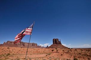 アメリカ国旗とビュートやメサ(台地)があるモニュメントバレーの写真素材 [FYI01561690]