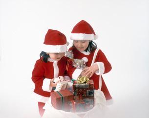 プレゼントの袋をのぞき込むサンタの服を着た女の子の写真素材 [FYI01561996]