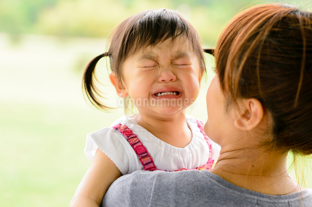 母親に抱かれる泣き顔の子どもの写真素材 [FYI01562063]