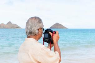 一眼レフカメラを持つシニア男性の後ろ姿の写真素材 [FYI01562108]