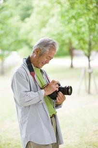 カメラを触るシニア男性の写真素材 [FYI01562116]