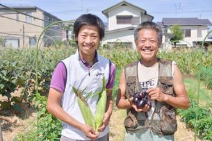 トウモロコシと寺島ナスを手に持つ男性の写真素材 [FYI01562564]