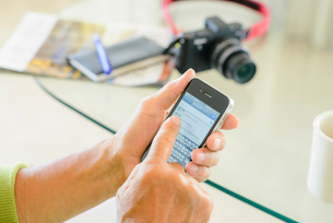 スマートフォンを操作するシニア男性の手の写真素材 [FYI01562681]
