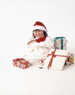 プレゼントの袋に入るサンタの服を着た女の子の写真素材 [FYI01562723]