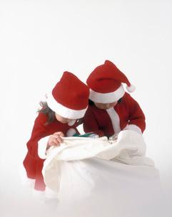 プレゼントの袋をのぞき込むサンタの服を着た女の子の写真素材 [FYI01562784]