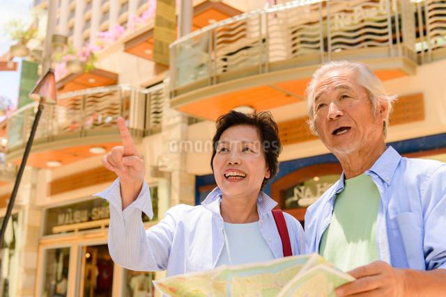 街頭で地図を見るシニア夫婦の写真素材 [FYI01563181]