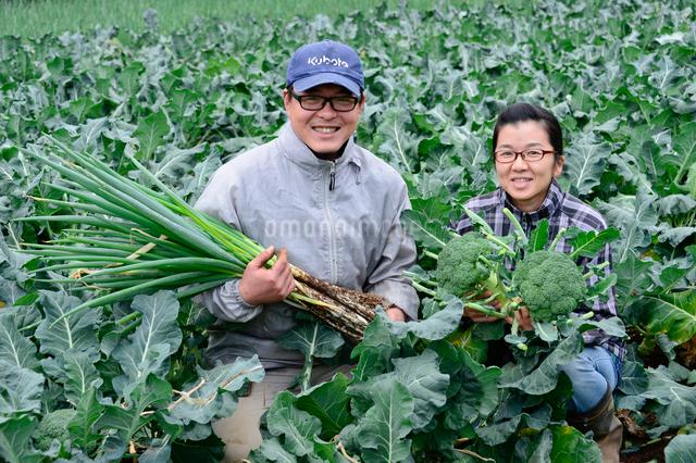 収穫したネギとブロッコリーを持つ農家夫婦の写真素材 [FYI01563386]