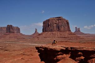 ビュートやメサ(台地)などがあるモニュメントバレーと乗馬客の写真素材 [FYI01563594]