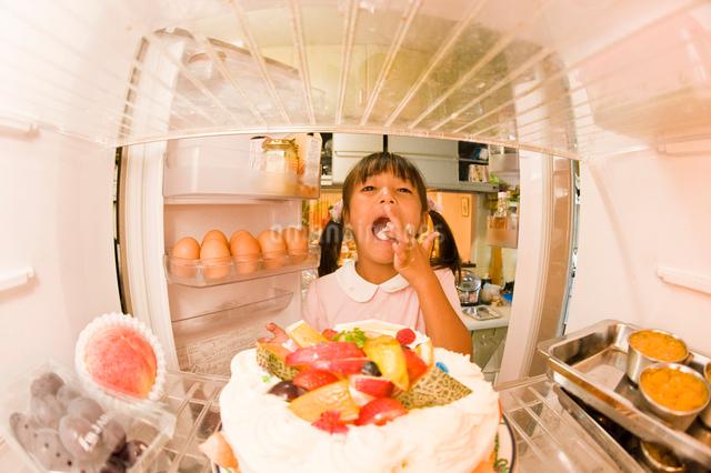 冷蔵庫のケーキをつまみ食いする女の子の写真素材 [FYI01564519]